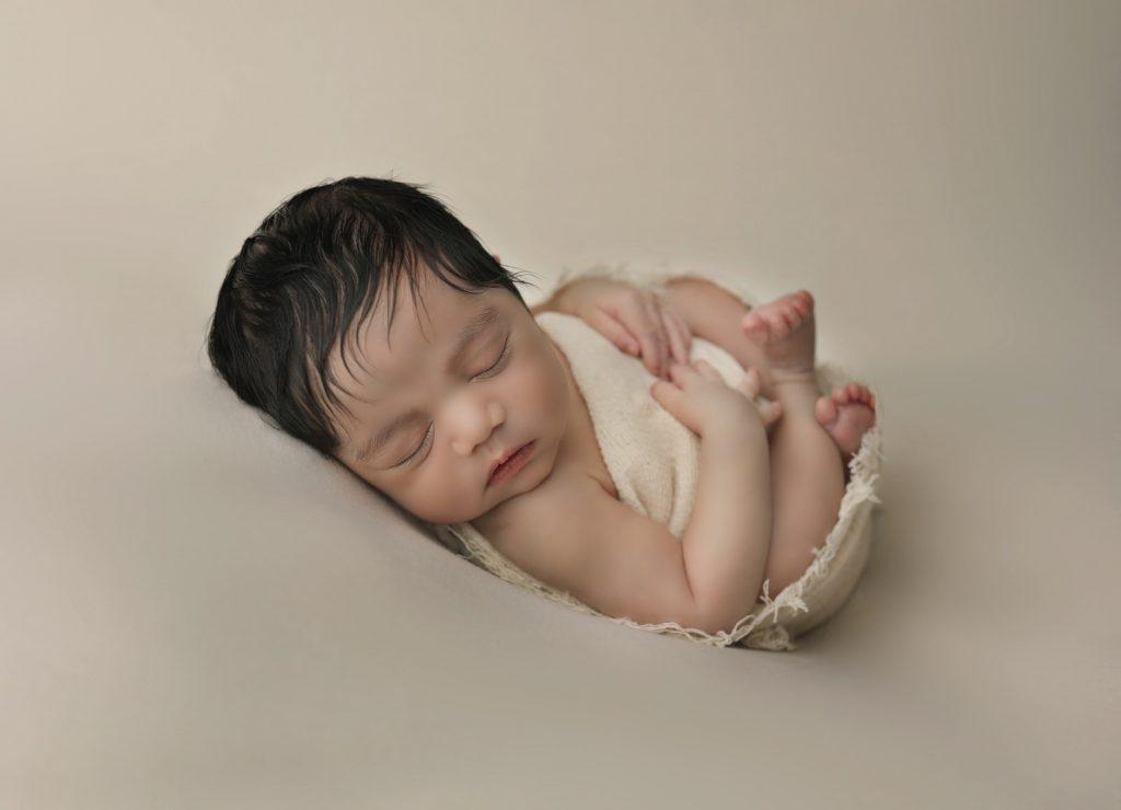 newborn baby boy portrait on simple cream background