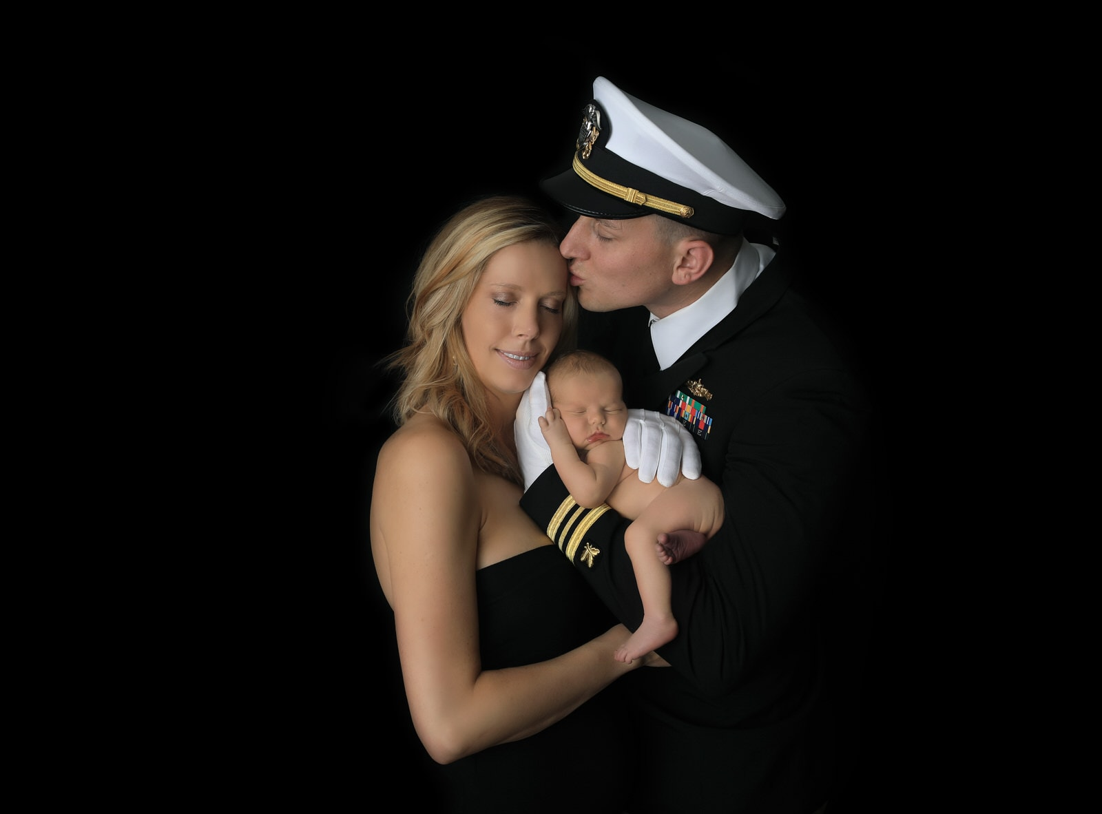 US navy dad poses in unifrom with newborn baby boy and mom at newborn photography session