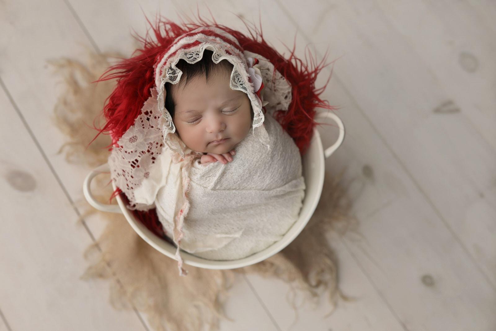 newborn baby pictured in white bucket