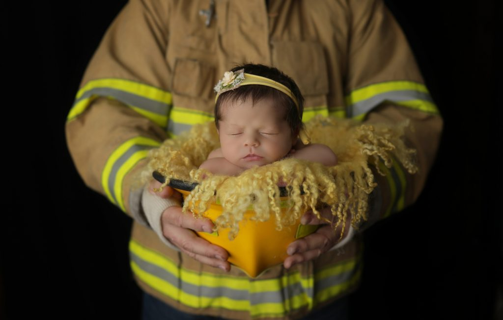 Firefighter dad poses with baby in his helmet during newborn session with harrisburg pa newborn photographer