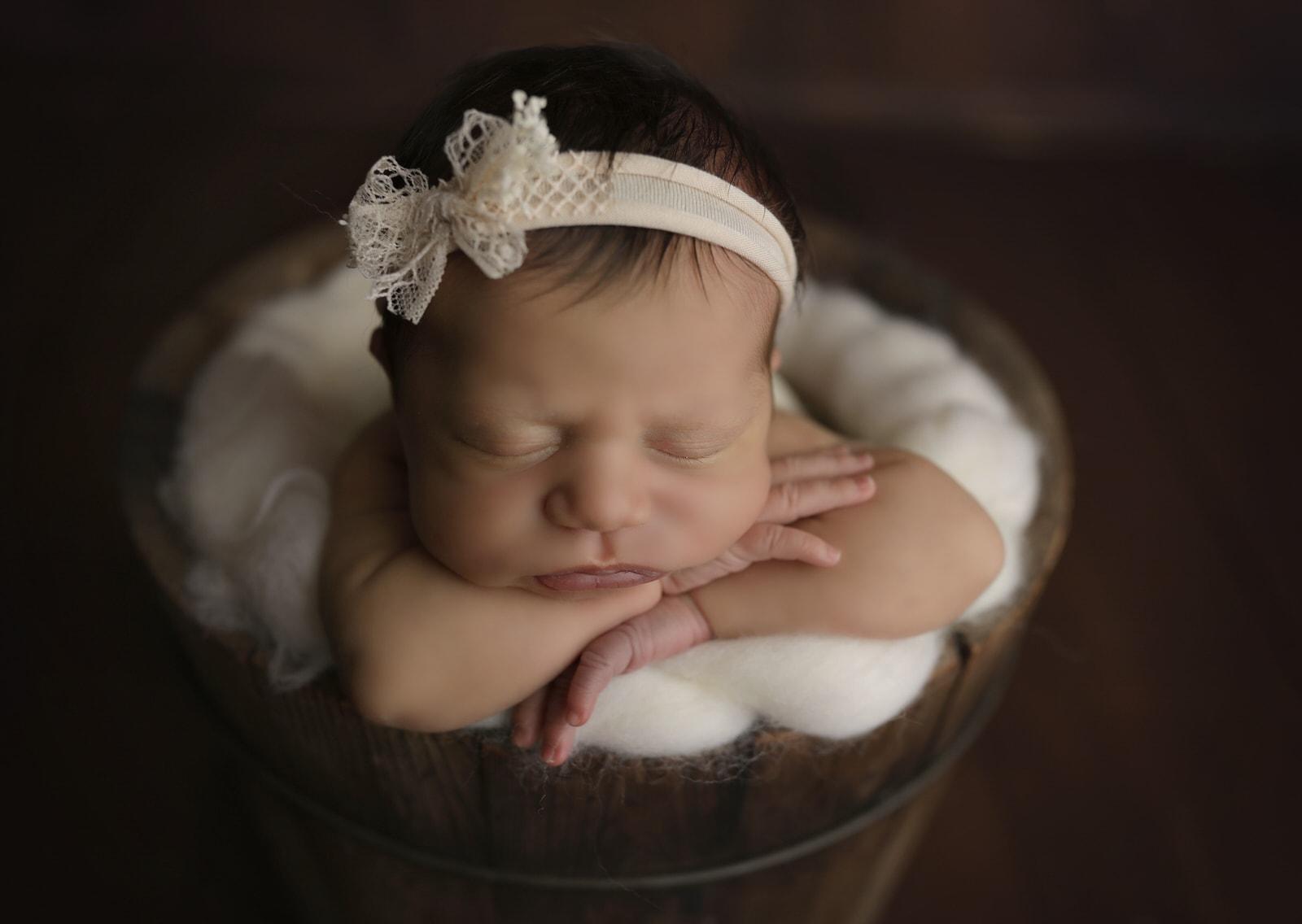 newborn baby sleeps in bucket during her newborn photoshoot in harrisburg pa