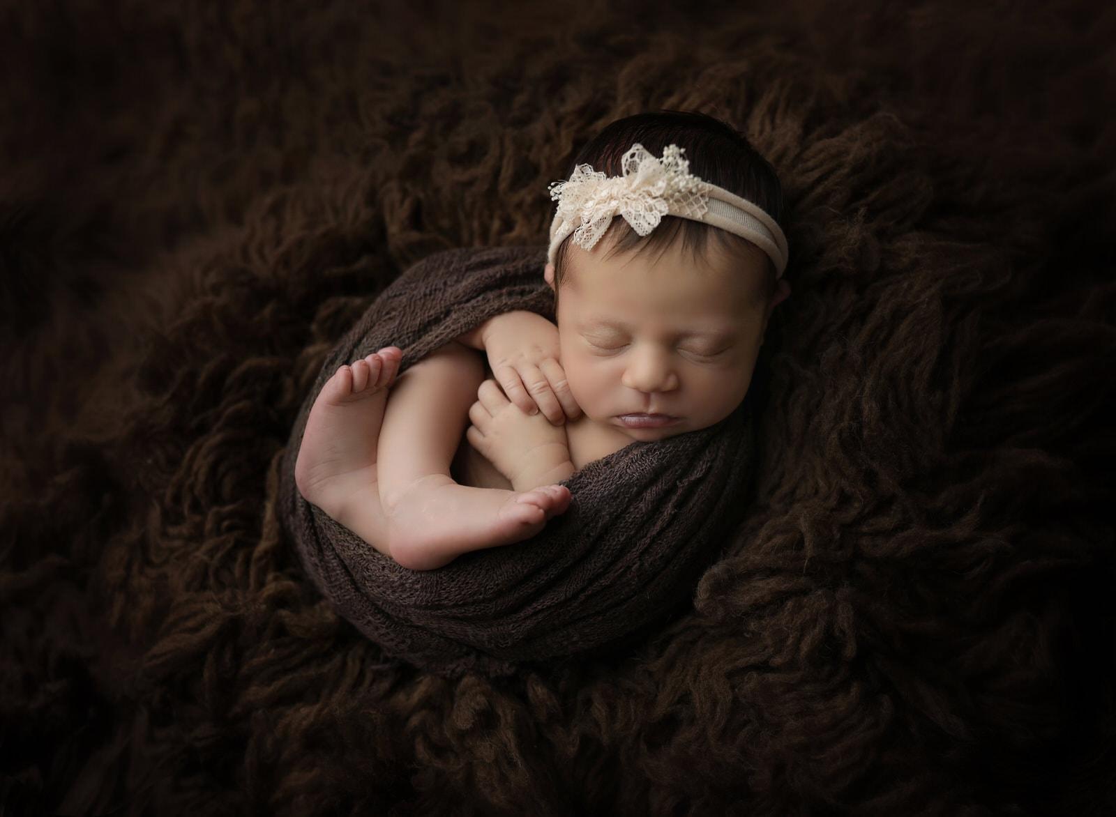 Karissa zimmer photography captures newborn girl on brown background near harrisburg pa