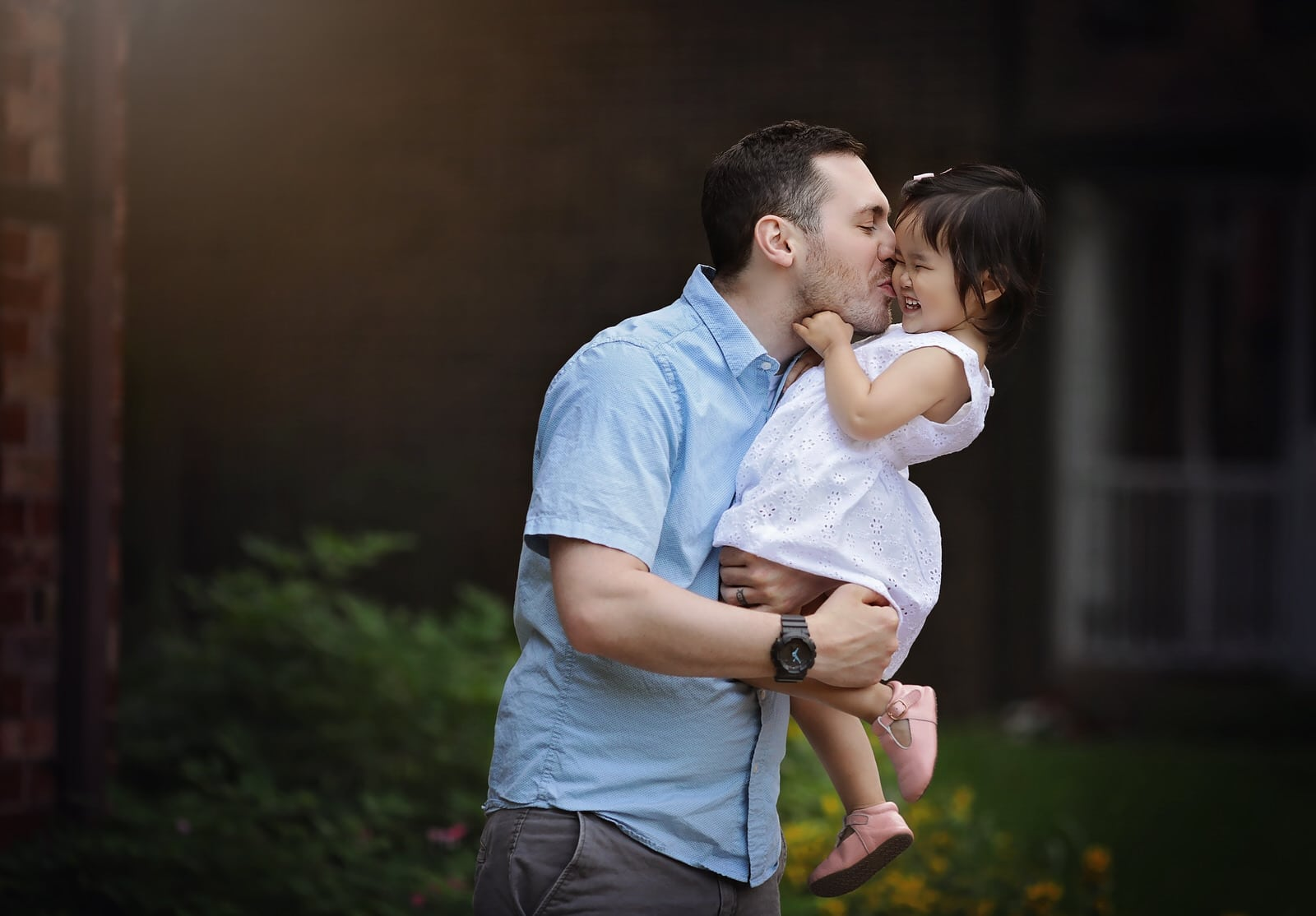 dad kisses his daughter on the cheek in sweet portrait by harrisburg family photographer