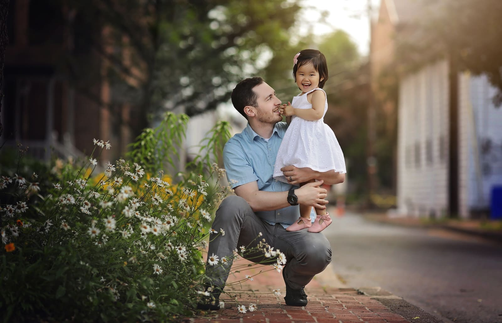 little girl stands on her dads knee during her summer family photography session in harrisburg pa