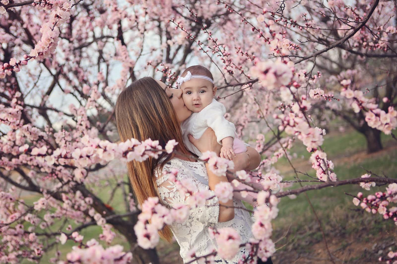 mom holds baby girl during outdoor spring portraits near harrisburg pa