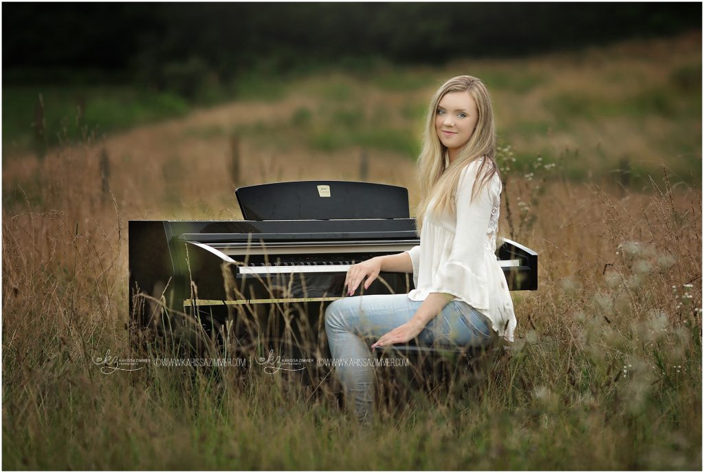 high senior girl photographed in field with piano in hummelstown pa