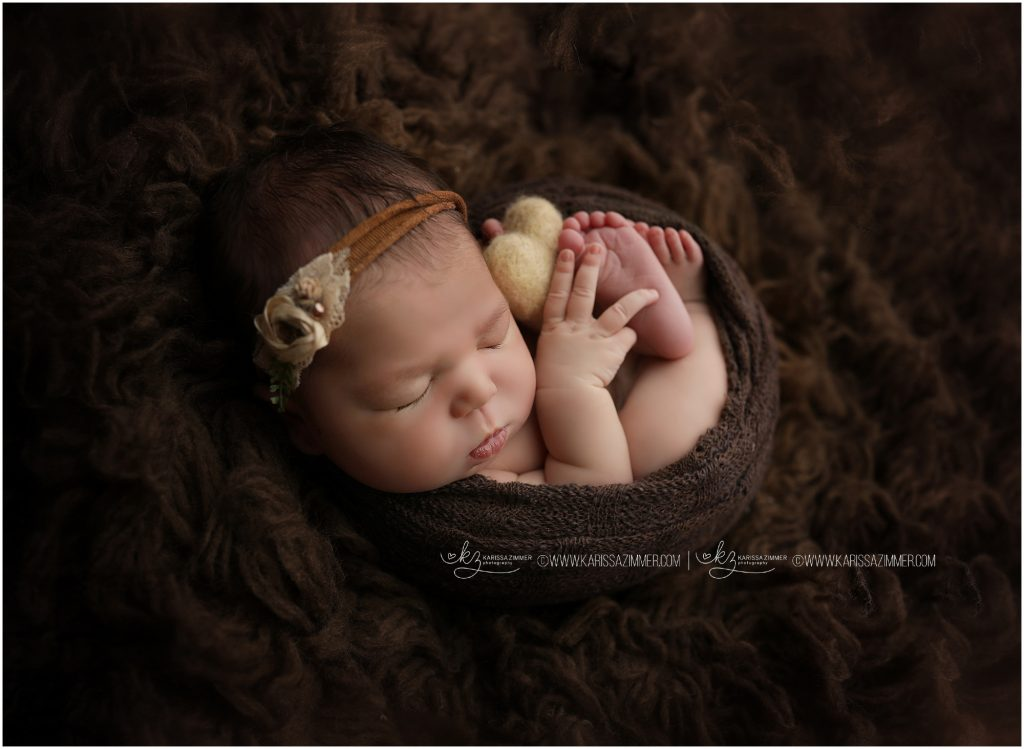 newborn baby girl posed with heart during newborn photography session