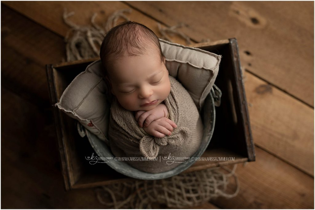 newborn baby boy is posed during his newborn photo session with karissa zimmer photography