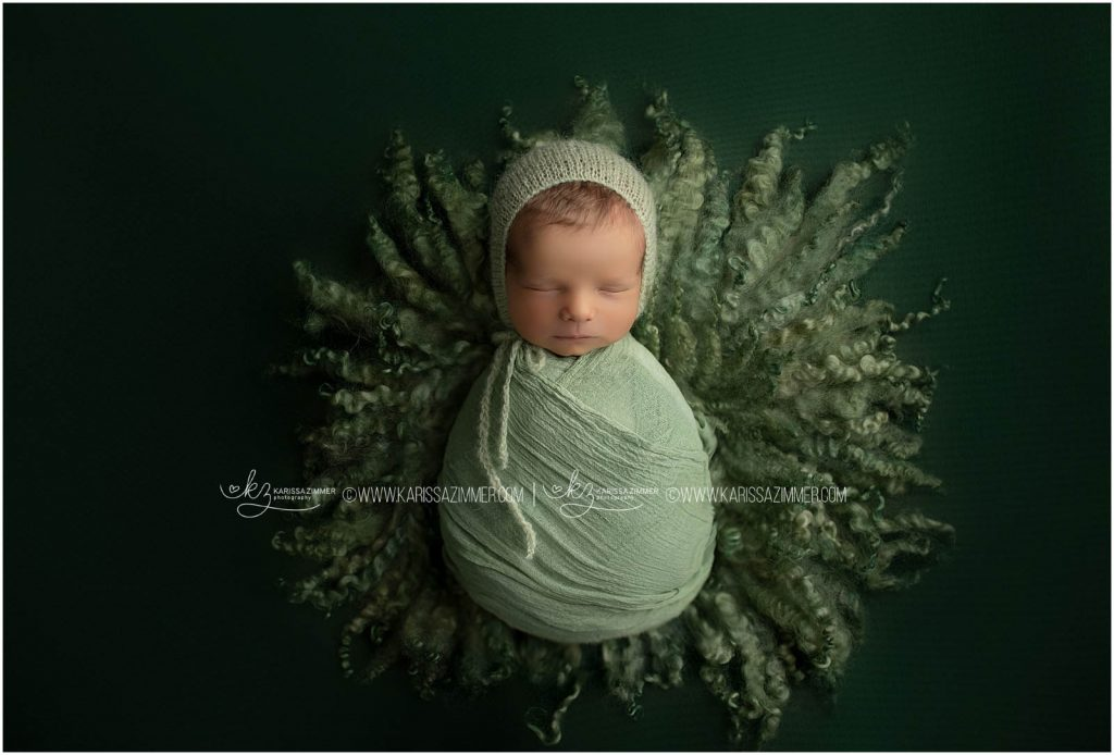 baby boy photographed on green by camp hill newborn photographer karissa zimmer photography