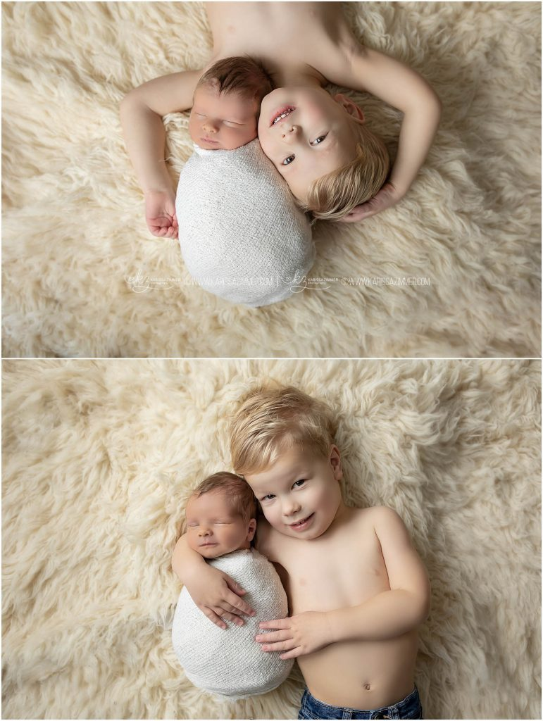 big brother poses at camp hill photography studio with his newborn baby brother